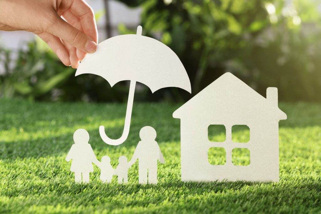 Woman holding paper umbrella over cutout of family and house on fresh grass, closeup. Life insurance concept