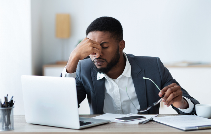 African businessman massaging his nose bridge, tired of long time work on laptop, copy space
